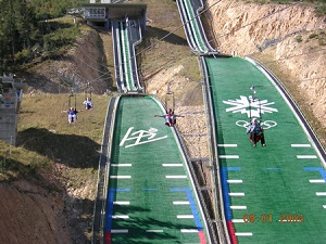 People Riding over Ecker Hill Alpine Skiing Tracks